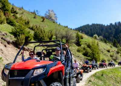 A tour group travels on ATVs and UTVs on the mountains