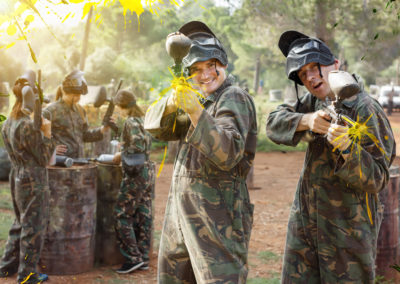 Two cheerful paintball players in full gear having fun outdoors